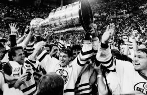 Edmonton Oilers team caption Wayne Gretzky is flanked by teammates as he skates with the Stanley Cup following their 3-1 victory over the Philadelphia Flyers in the seventh game of the Stanley Cup finals in Edmonton on May, 31, 1987. From left are Kent Nilsson, Gretzky and at far right Marty McSorley. (AP Photo/Larry Macdougal)
